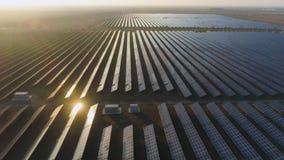 Großes Feld von photo-voltaischen Sonnenkollektoren bei Sonnenuntergang Sonnenlichtreflexion Schattenbild des kauernden Geschäfts stock footage