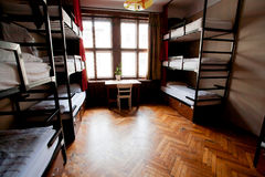 Großes Fenster im Schlafsaal der europäischen Herberge des Studenten mit waagerecht ausgerichteten Betten Lizenzfreies Stockbild