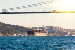 Großes Frachtschiff, das entlang dem Bosphorus-Kanal auf dem Hintergrund der Brücke auf dem Hintergrund fortfährt stockbild