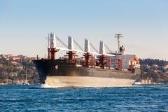 Großes Frachtschiff, das entlang dem Bosphorus-Kanal auf dem Hintergrund der Küste auf dem Hintergrund fortfährt lizenzfreies stockfoto