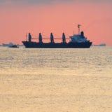 Großes Frachtschiff eskortiert Stockfoto