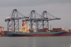 Großes Frachtschiff mit den Behältern, die durch Kran am Hafen laden Lizenzfreies Stockbild