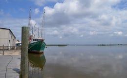 Großes Garnelenboot am Dock durch offenes Wasser stockfotografie