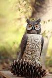 Großes gehörntes Owl Sculpture mit einem Kiefernkegel Lizenzfreies Stockfoto