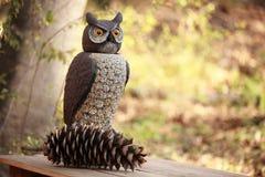 Großes gehörntes Owl Sculpture mit einem Kiefernkegel Lizenzfreie Stockfotografie