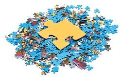 Großes gelbes Stück auf Stapel von Puzzlespielen Lizenzfreies Stockbild