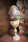 Großes gemaltes Ei in einem Stand auf einem Hintergrund des roten Backsteins lizenzfreie stockbilder
