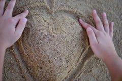 Großes Herz, das durch Hände vom Sand auf dem Strand macht Beschneidungspfad eingeschlossen Stockfotografie