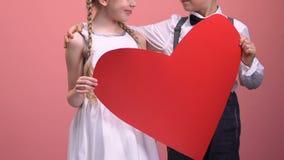 Großes Herz haltene und umarmende Kinderpaare, romantisches Datum am Valentinsgrußtag stock video