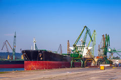 Großes industrielles Frachtschiff lädt im Hafen Stockbild