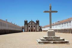 Großes Kreuz mit Kirche im Hintergrund Stockbilder