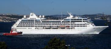 Großes Kreuzfahrtschiff mit dem Versuchsschiff, das es aus Hafen heraus führt Stockfotografie