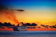 Großes Kreuzschiff auf ruhigem See bei Sonnenuntergang Lizenzfreies Stockbild