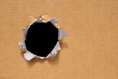 Großes Loch auf einer starken neuen braunen Pappe Großes schwarzes Loch für Text Stockbilder