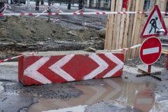 Großes Loch in der Straße hergestellt für die Straße, die Arbeiten mit Vorsichtzeichen repariert Stockfotografie