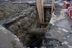 Großes Loch in der Straße hergestellt für die Straße, die Arbeiten mit Vorsichtzeichen repariert Stockfotos