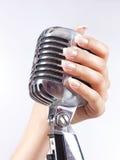 Großes Mikrofon in der Hand der Frau Stockfotos