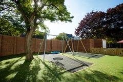 Großes modernes Schwingen in einem ummauerten Garten mit einem großen Baum im Sonnenschein lizenzfreie stockbilder