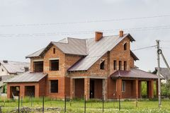 Großes modernes zwei-berühmtes nicht beendeten neues Ziegelsteinfamilien-Häuschenhaus mit steilem braunem geschichtetem Dach, Gar lizenzfreie stockbilder