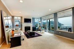 Großes offenes Buchtwohnzimmer mit Kamin, Fernsehen und modernen Möbeln. Stockbilder