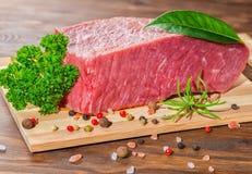 Großes rohes knochenloses Rindfleischfleisch mit Pfeffer, Rosmarin, Petersilie, Laure stockfotos