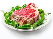 Großes rohes Kotelett der Kuh mit grünen Paprikas lizenzfreie stockfotos