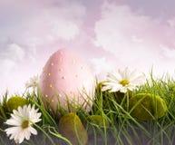 Großes rosafarbenes Ostern mit Blumen im hohen Gras Stockfotografie