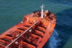 Großes rotes Frachtschiff, das auf tiefen blauen Ozean fährt Lizenzfreies Stockbild