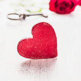 Großes rotes hölzernes Herz über rosafarbenem und Schlüsselhintergrund Stockfotografie
