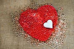 Großes rotes Herz, kleines weißes Herz und viel kleine Glaskugel Lizenzfreies Stockfoto