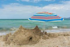 Großes Sandburg und Regenschirm auf dem Strand mit Meer im Hintergrund stockfotografie