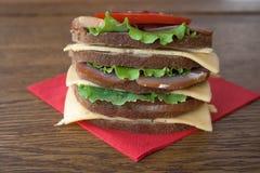 Großes Sandwich mit Speck und Käse und Frischgemüse auf der Weinlese hölzern Stockbilder