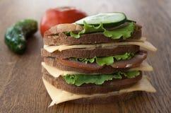 Großes Sandwich mit Speck und Käse und Frischgemüse auf der Weinlese hölzern Lizenzfreie Stockfotos