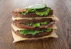 Großes Sandwich mit Speck und Käse und Frischgemüse auf der Weinlese hölzern Lizenzfreie Stockbilder