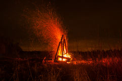 Großes schönes Lagerfeuer im Nachtwald, den viele hellen Funken in alle Richtungen fliegen Lizenzfreie Stockfotos