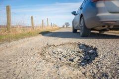 Großes Schlagloch auf einer Landstraße mit dem Führen des Autos lizenzfreie stockfotos