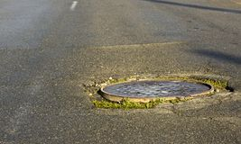 Großes Schlagloch im Asphalt und im Kreiskanaldeckel des Abwassers gut in der Straße, Lizenzfreies Stockfoto