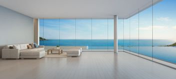 Großes Sofa auf Bretterboden nahe Glasfenster- und Swimmingpool mit Terrasse an der Penthauswohnung, Aufenthaltsraum im Seeansich lizenzfreie abbildung