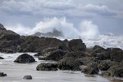 Großes Spritzen in einem felsigen leeren Strand Stockfotos