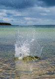 Großes Spritzen im Wasser mit ursprünglichem Meer im Hintergrund stockbild