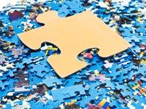 Großes Stück auf Stapel von auseinandergebauten Puzzlespielen Stockbild