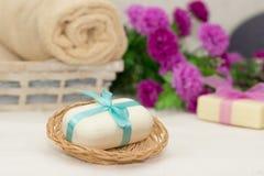 Großes Stück beige Seife im busket, witn in blauem Bogen, in den Blumen und in t Stockbild