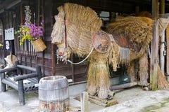 Großes Strohpferd mit einem traditionellen Hut in Tsumago, Japan Stockbilder