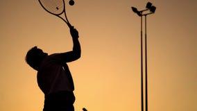 Großes Tennis des gesunden Lebensstils und des aktiven Restes Der Athlet steht auf dem Hintergrund eines orange Sonnenuntergangs  stock video footage