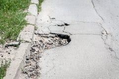Großes tiefes gefährliches Loch in der Asphaltstraße, Gefahr für das Autofahren kann einen Unfall oder einen Zusammenbruch des Fa lizenzfreie stockfotos