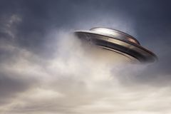 Großes UFO, das von den Wolken auftaucht Lizenzfreies Stockbild