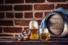 Großes und kleines Bier Oktoberfest mit hölzernem Fass der Brezel und blauer Tischdecke stockbilder