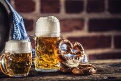 Großes und kleines Bier Oktoberfest mit hölzernem Fass der Brezel und blauer Tischdecke lizenzfreies stockfoto