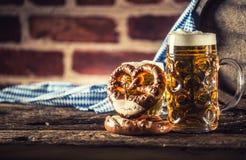 Großes und kleines Bier Oktoberfest mit hölzernem Fass der Brezel und blauer Tischdecke stockbild
