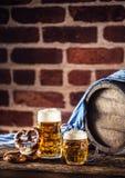 Großes und kleines Bier Oktoberfest mit hölzernem Fass der Brezel und blauer Tischdecke lizenzfreie stockfotos